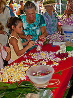 Child and Hawaiian aunty lei making at King Kamehameha Day Parade festival, King Kamehameha Park, North Kohala, town of Kapa'au.