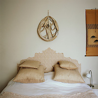 A white bedroom with a double bed with cushions and crocheted bed cover, the design of which is reflected in the painted headboard.