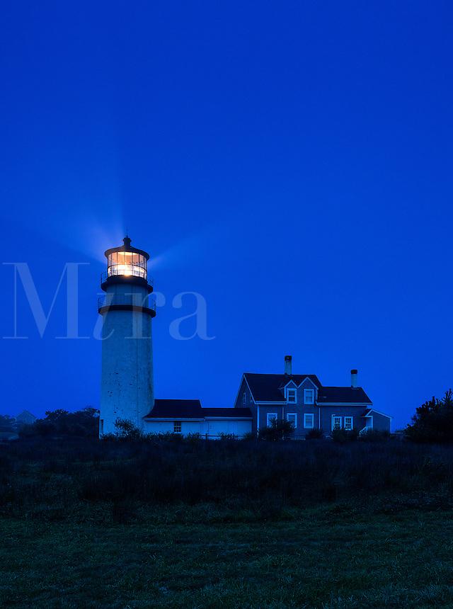 Lighthouse casts guiding light into dark blue night, Truro, Cape Cod, Massachusetts, USA