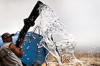 A Peruvian water distribution worker with a hose splashes drinking water from a truck in Pachacútec, a desert suburb of Lima, Peru, 21 January 2015. Although Latin America (as a whole) is blessed with an abundance of fresh water, having 20% of global water resources in the the Amazon Basin and the highest annual rainfall of any region in the world, an estimated 50-70 million Latin Americans (one-tenth of the continent's population) lack access to safe water and 100 million people have no access to any safe sanitation. Complicated geographical conditions (mainly on the Pacific coast), unregulated industrialization (causing environmental pollution) and massive urban poverty, combined with deep social inequality, have caused a severe water supply shortage in many Latin American regions.