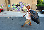 Sadedin Husein, 63, is a Roma man who lives in the mostly Roma town of Suto Orizari, Macedonia, but spends his days at work collecting plastic bottles in the streets of Skopje, which he sells to recyclers. Here he walks along a Skopje street with his bag full of plastic bottles.