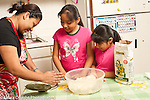 FAmily cooking at home mother showing daughters ages 6 and 9 how to make tortillas