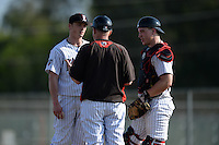 Edgewood Eagles head coach Al Brisack talks with pitcher Blake Bieri (21) and catcher Garrett Bogucki (25) during the first game of a doubleheader against the UW-Stout Blue Devils on March 16, 2015 at Lee County Player Development Complex in Fort Myers, Florida.  UW-Stout defeated Edgewood 6-1.  (Mike Janes/Four Seam Images)