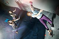 Group of female climbers climbing at an indoor climbing wall.