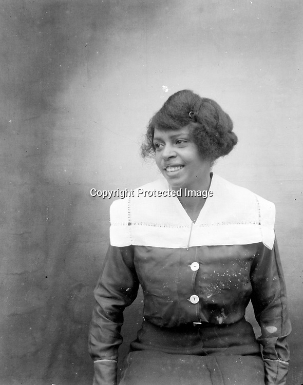 """MATRON. John Johnson set his tripod unusually distant from his subject, creating an unusual image in which the wide brick sidewalk and the """"clouded"""" backdrop became vital elements of the composition.<br /> <br /> Photographs taken on black and white glass negatives by African American photographer(s) John Johnson and Earl McWilliams from 1910 to 1925 in Lincoln, Nebraska. Douglas Keister has 280 5x7 glass negatives taken by these photographers. Larger scans available on request."""