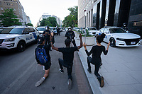Demonstrators kneel in front of a police officer during a protest near the White House in Washington, D.C., U.S., on Monday, June 1, 2020, following the death of an unarmed black man at the hands of Minnesota police on May 25, 2020.  More than 200 active duty military police were deployed to Washington D.C. following three days of protests.  Credit: Stefani Reynolds / CNP/AdMedia