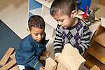 Education Preschool 3-4 year olds two boys building together wooden block construction