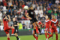 USWNT midfielder Tobin Heath (17) heads the ball.