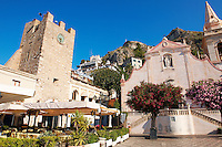 St. Guiseppi church and gate tower on  on the Plaza ix Aprile with trees in blossom - Taormina, Sicily