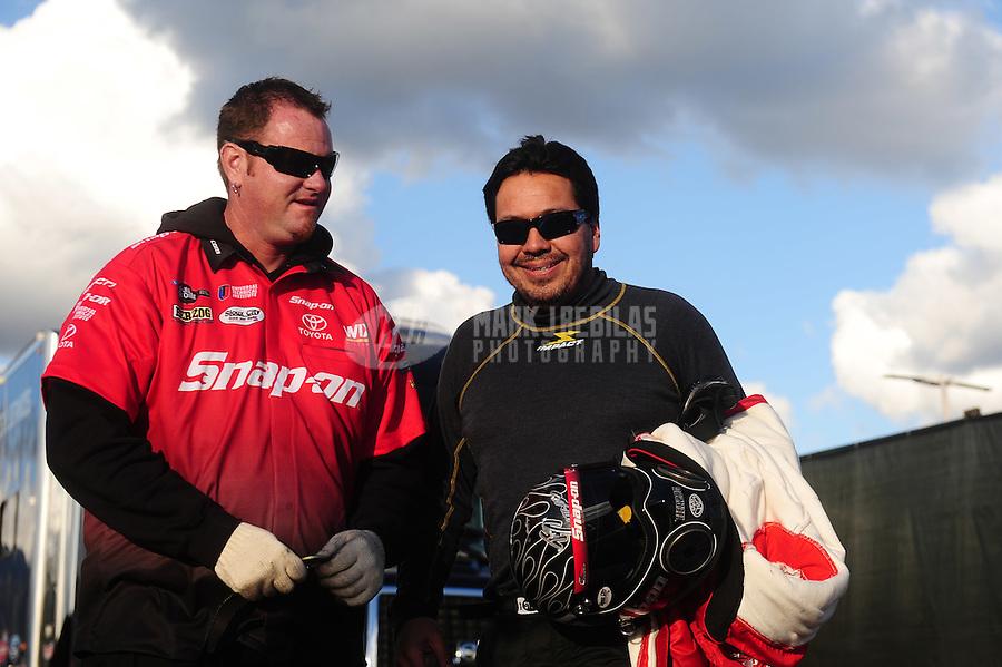 Feb. 26, 2011; Pomona, CA, USA; NHRA funny car driver Cruz Pedregon (right) with a crew member during qualifying at the Winternationals at Auto Club Raceway at Pomona. Mandatory Credit: Mark J. Rebilas-.