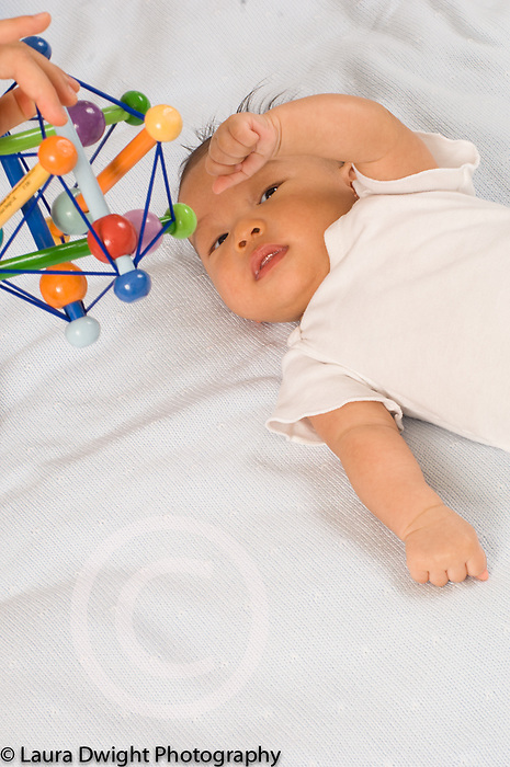 2 month old baby boy batting at dangled toy vertical