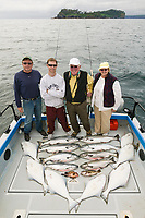 Visitors stand by their catch of the day while charter fishing for salmon and halibut in the coastal community of Sitka, Alaska.