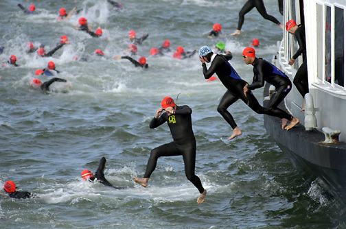 """PICO VAN HOUTRYVE/Examiner 6.10.01 news: Triatheletes in wet suits and swim caps jump from the port side of the California Hornblower at the start of the 21st annual """"Escape from Alcatraz"""" triathalon in the San Francisco Bay near Alcatraz Island, Sunday, June 10, 2001."""