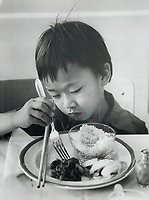 1979 FILE PHOTO - ARCHIVES -<br /> <br /> War - Vietnam War - Refugees in Canada ; <br /> Quach Phen; 7; tries a fork for first time<br /> <br /> <br /> Bezant, Graham<br /> Picture, 1979, <br /> <br /> 1979,<br /> <br /> PHOTO : Graham Bezant - Toronto Star Archives - AQP