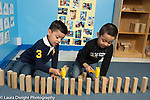 Education Preschool 4 year olds two boys using toy plastic hammers to pound fence they build out of wooden blocks