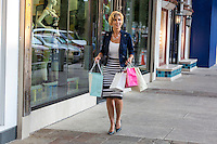 Beautiful sexy woman shops and holds bags at an outdoor shopping mall in Austin, Texas.