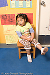 Education Preschool 3-4 year olds time out girl sitting on time out chair kicking feet not subdued vertical