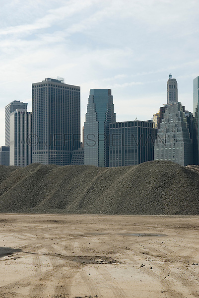AVAILABLE FROM JEFF AS A FINE ART PRINT.<br /> <br /> AVAILABLE FROM PLAINPICTURE.COM FOR COMMERCIAL AND EDITORIAL LICENSING.  Please go to www.plainpicture.com and search for image # p5690153.<br /> <br /> Pile of gravel at Brooklyn Construction Site, with Lower Manhattan Skyline Visible in the Distance<br /> <br /> New York City, New York State, USA