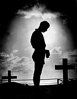 Silhouetted in the golden glory of a Pacific sunrise, crosses mark the graves of American boys who gave their lives to win a small atoll on the road to the Philippines.  A Coast Guardsman stands in silent reverence beside the resting place of a comrade.  1944. (Coast Guard)<br /> Exact Date Shot Unknown<br /> NARA FILE #:  026-G-3971<br /> WAR & CONFLICT BOOK #:  1350