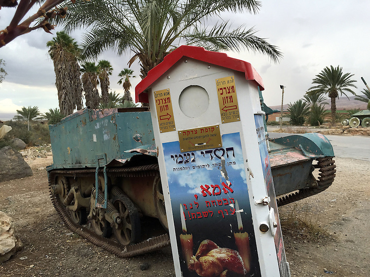 """10. """"Charity for the Orphans and Widows"""": alms box with abandoned tank outside cafe, Jordan Valley.<br /> <br /> Maintained by the Charities of Naomi, this alms box is designed for weekly collection of non-perishable foodstuffs for orphans and widows. Yet it tilts crazily as if it's been hit by the abandoned tank behind it. I was struck by the incongruity of """"chesed"""" or """"loving kindness,"""" paired with the violent legacy of the tank. Moreover, the picture of the plump roasted chicken with candles is accompanied by these words:  """"Mother, you promised us a chicken for the Sabbath."""" If the children are orphaned and the mother widowed, this is indeed a grim reminder of the casualties of war."""