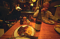 In a restaurant in Nimes with a plate with a big red stake and a potato gratin, a bottle of Domaine Leon Barral Faugeres, a red wine glass, another dinner guest drinking a glass of wine. Coloured lamps. Le Wine Bar Chez Michel - a popular restaurant of a more basic 'bistro' style. But with an excellent wine list.  Nimes, Gard, Provence, France, Europe