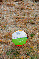 """A beachball with handwritten messages, including """"Trump 2020,"""" lays in the grass as people wait in line to enter a Make America Great Again Victory Rally with US President Donald Trump in the final week before the Nov. 3 election at Pro Star Aviation in Londonderry, New Hampshire, on Sun., Oct. 25, 2020. Many wore MAGA hats and other Donald Trump paraphernalia. An attendee had passed around the ball for people to write messages on, but balls are prohibited items for people to bring in to Trump rallies so it got left behind."""