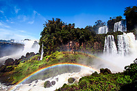 Beautiful Iguazu Falls cataracts under a blue sky, with double rainbow across the river rapids, in Iguacu National Park, Iguazu, Brazil and Argentina