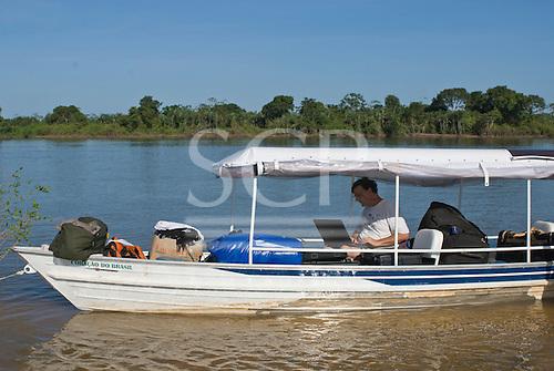 Xingu Indigenous Park, Mato Grosso State, Brazil. Patrick Cunningham working on a laptop computer aboard the 'Coração do Brasil'.