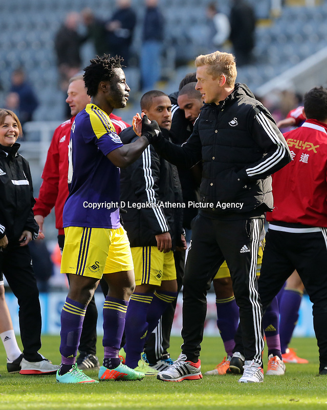 Pictured: Swansea head coach Garry Monk (R) takes to the pitch to congratulate double scorer Wilfried Bony (L) after the final whistle. Saturday 19 April 2014<br /> Re: Barclay's Premier League, Newcastle United v Swansea City FC at St James Park, Newcastle, UK.