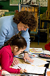 Education Elementary Grade 2 female science specialist working with female student vertical