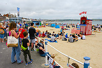 BNPS.co.uk (01202 558833)<br /> Pic: Graham Hunt/BNPS<br /> <br /> Holidaymakers watching the traditional Punch and Judy show at the beach on a warm overcast afternoon at the seaside resort of Weymouth in Dorset.<br /> <br /> Britain's seaside resorts could lose their last remaining Punch and Judy shows because of shocking abuse from onlookers.<br /> <br /> The iconic century old tradition is at risk of extinction as two of the country's last three shows are bombarded by insults from angry families refusing to donate just £2 to watch.<br /> <br /> Such donations are essential for the survival of the puppet shows, which rely entirely on public generosity to keep going.