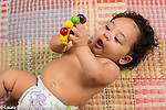 3 month old baby girl closeup on back grasping toy