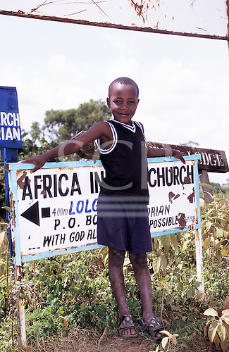 Lolgorian, Kenya. Portrait of a young boy in t-shirt and shorts in front of a sign to a church.