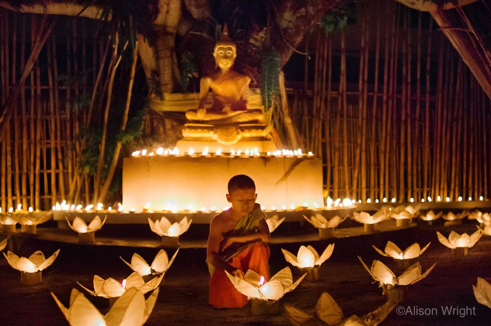 Monks lighting candles and khom loy lanterns for Loi Krathong festival.