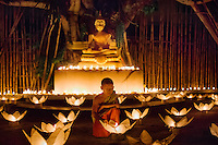 Monks lighting candles and khom loy lanterns for Loi Krathong festival.