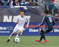 New England Revolution defender Kelyn Rowe (11) brings the ball forward.   In a Major League Soccer (MLS) match, Sporting Kansas City (blue) tied the New England Revolution (white), 0-0, at Gillette Stadium on March 23, 2013.