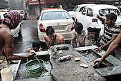 Street dwellers wash themselves and the cars on the streets of Kolkata in West Bengal, India.