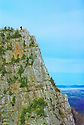 A hiker/photographer is dwarfed in the landscape atop Table Rock in New Hampshires Dixville Notch.