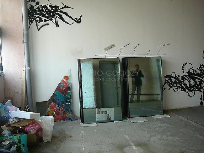 Des travaux à venir dans l'atelier Bázis où ces vitres seront placées. Pour le moment, elles restent dans le couloir, se mélangeant ainsi aux élément stagnants du lieu.