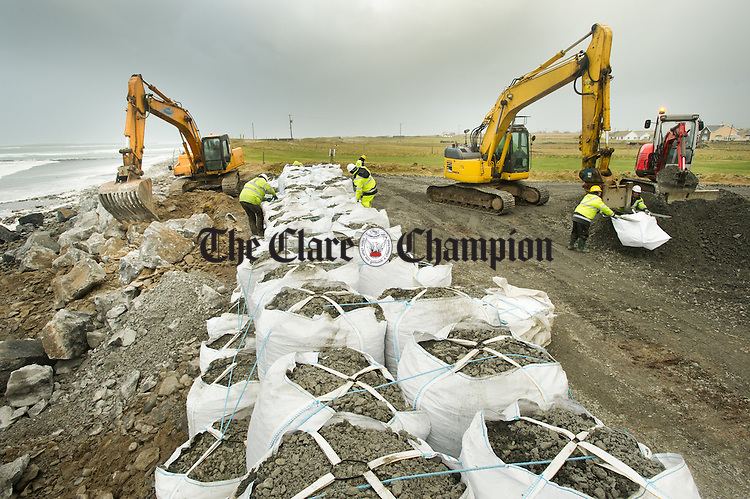 County Council workers battle with the elements as they erect a temporary flood barrier of gravel bags and rock armour, at the rear of the houses which were damaged in the recent storms at Tromora, Seafield, Quilty in preparation for further high tides expected in the coming days. Photograph by John Kelly.