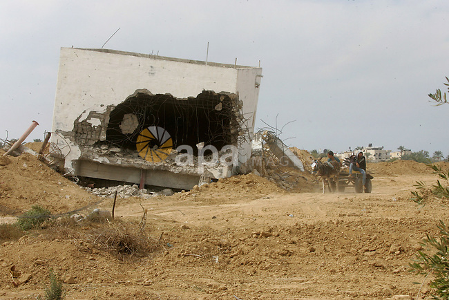 A Palestinian boy rides donkey cart in front of International Committee of the Red Cross (ICRC), as the comittee assists Palestinian farmers to repair their fields that were devastated during the Israeli army summer's military offensive on the Gaza Strip on October 22, 2014, in Khan Yunis' Khuzaa neighbourhood in the southern Gaza Strip near the Israeli border. Photo by Abed Rahim Khatib