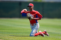 Philadelphia Phillies infielder Gustavo Gonzalez (13) throws to first from his knees during a minor league Spring Training game against the New York Yankees at Carpenter Complex on March 21, 2013 in Clearwater, Florida.  (Mike Janes/Four Seam Images)