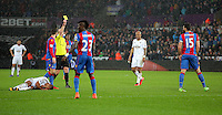 Match referee Mike Dean shows a yellow card to Mile Jedinak of Crystal Palace (R) brought down Wayne Routledge (L) of Swansea during the Barclays Premier League match between Swansea City and Crystal Palace at the Liberty Stadium, Swansea on February 06 2016