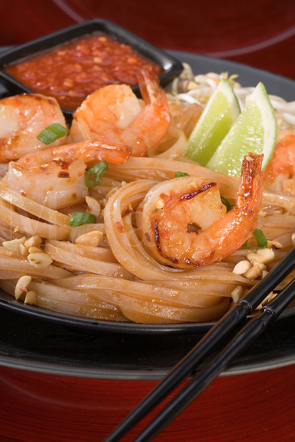 Pad Thai, Asian Noodles with Shrimps, peanuts, and green onions. Served on a black plate with a red background and chop sticks