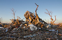 A destroyed vehicle is found bent against the remains of a tall tree in a residential neighborhood of Moore Oklahoma after the passage of a deadly EF-5 tornado on May 20th, 2013.