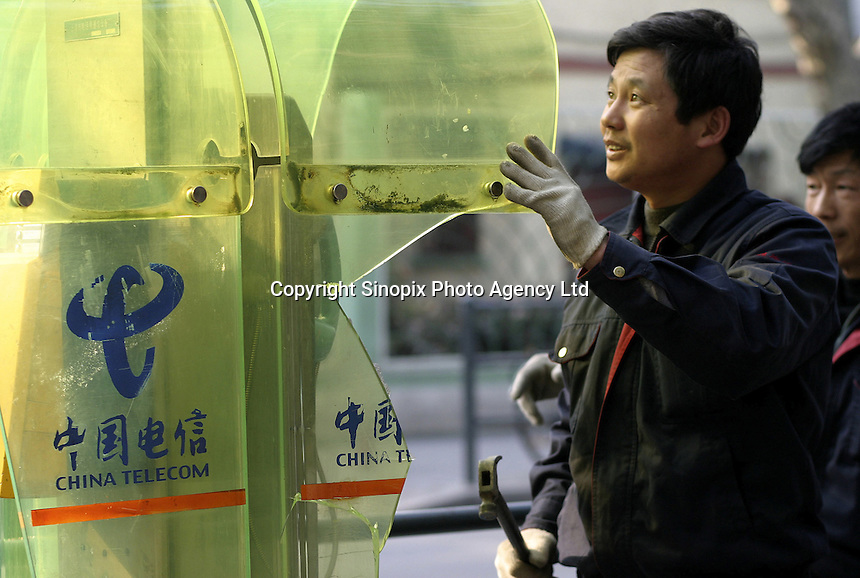 A Chinese worker knocks down a China Telecom phone booth for the installation of new ones on a street in Shanghai, China. China telecom is the country's dominant land-line based telecomunications provider and also holds a large market share in Internet related services..