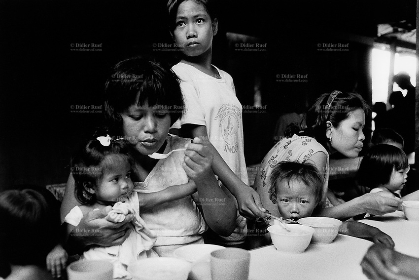 """Philippines. Luzon Region. Manila. Tondo area. Smokey mountain is a rubbish dump. Life on a garbage heap. Feeding center for malnourished children at the catholic church """" Grace children save"""". Families, mothers and kids, sisters and brothers. Food. © 1992 Didier Ruef ."""