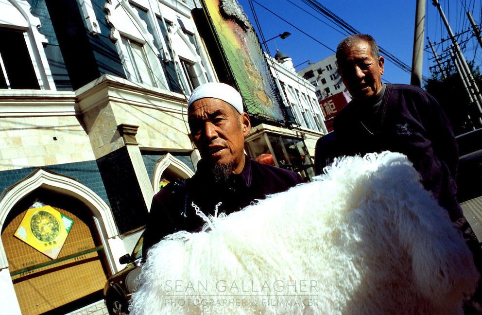 CHINA. Beijing. A man selling goods in the Muslim district of 'Niu Jie'. 2005