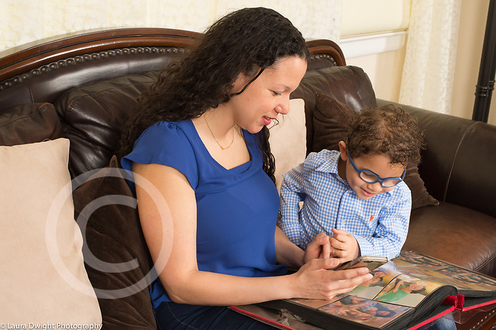3 year old boy at home with mother, looking at photograph album and photos on cell telephone