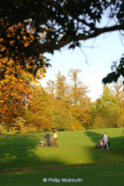 Mothers with push-chairs walk in Golders Hill Park, which is managed by the Corporation of London.